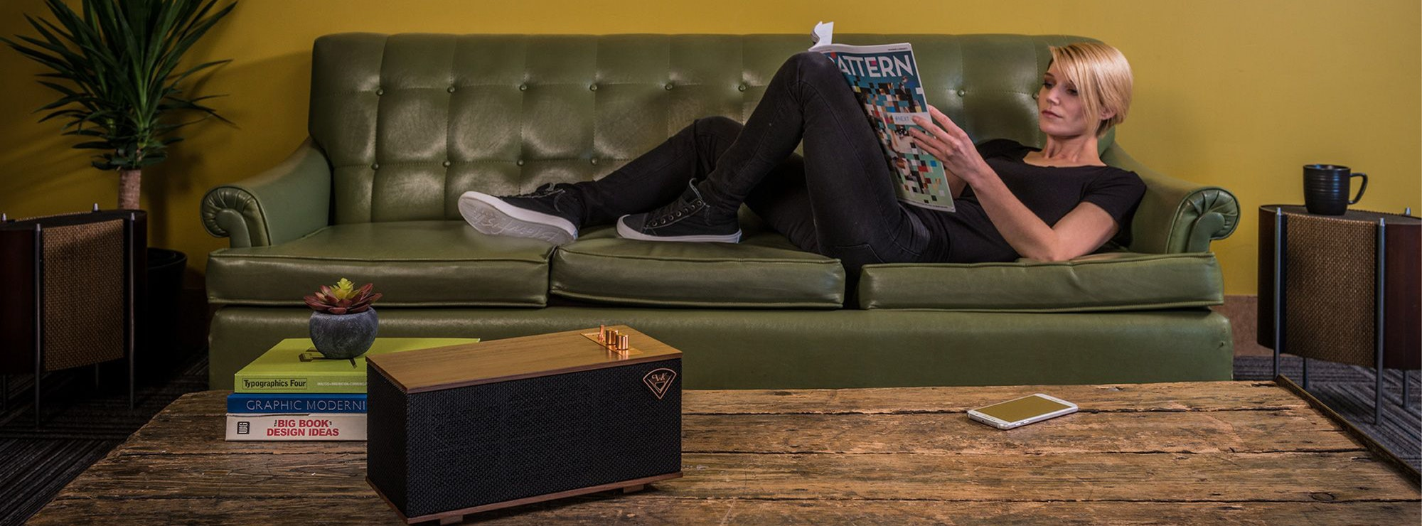 Lady reading a magazine on the couch listening to a Klipsch wireless speaker