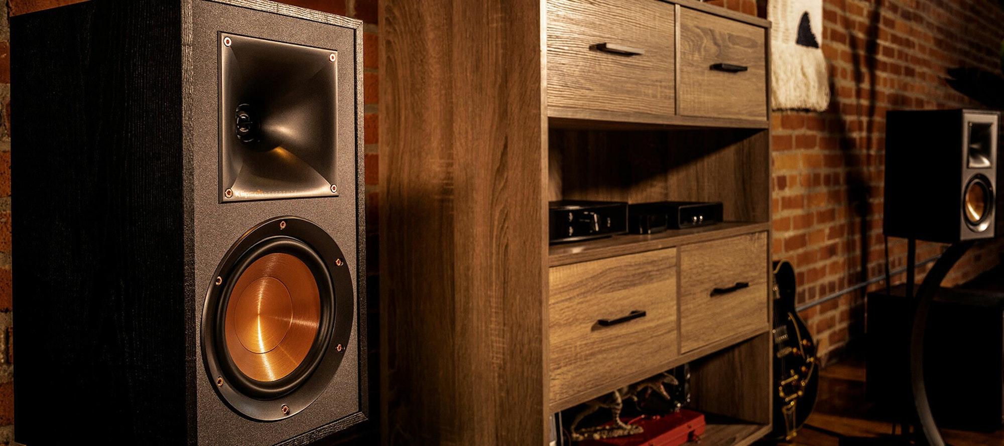 Klipsch bookshelf speakers home setup next to brick wall