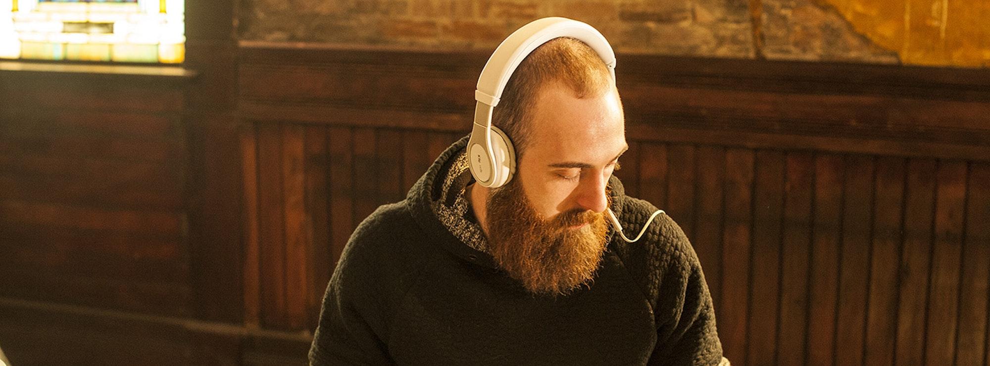 Bearded man listening to Klipsch headphones