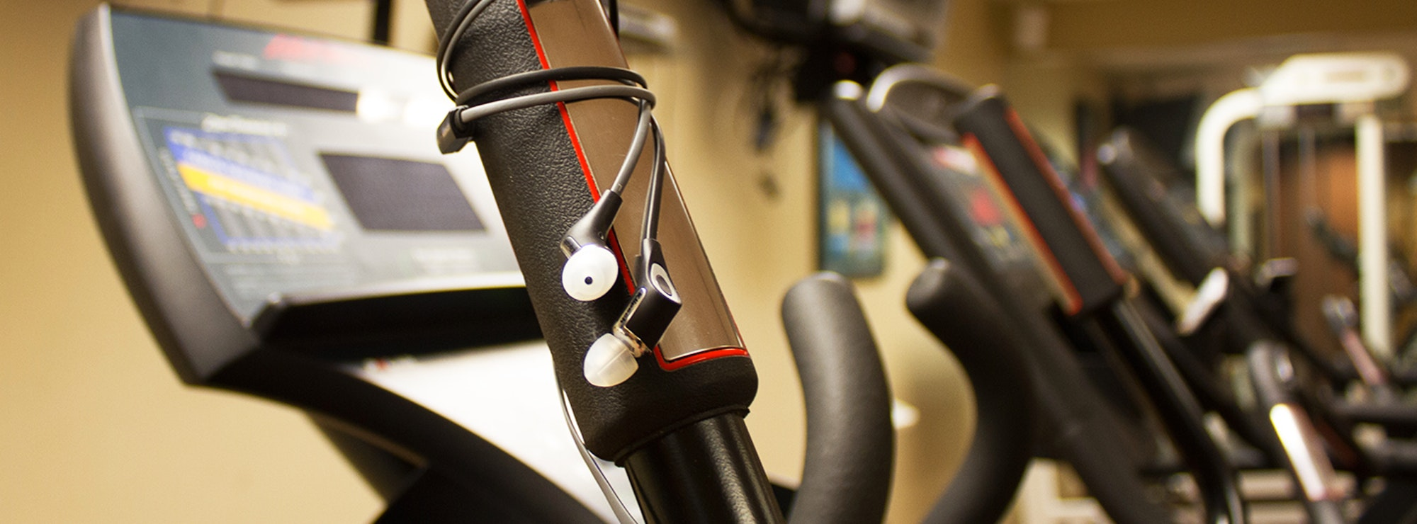 Klipsch in ear headphones wrapped around the handle of workout equipment