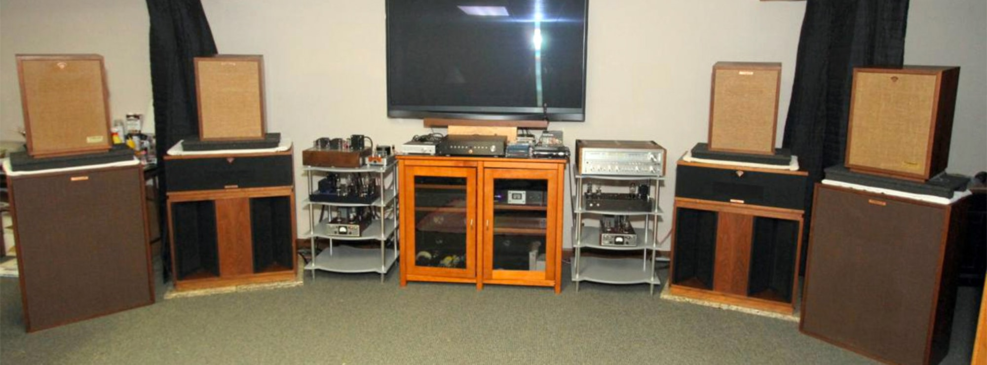 A variety of Klipsch speakers surrounding a tv