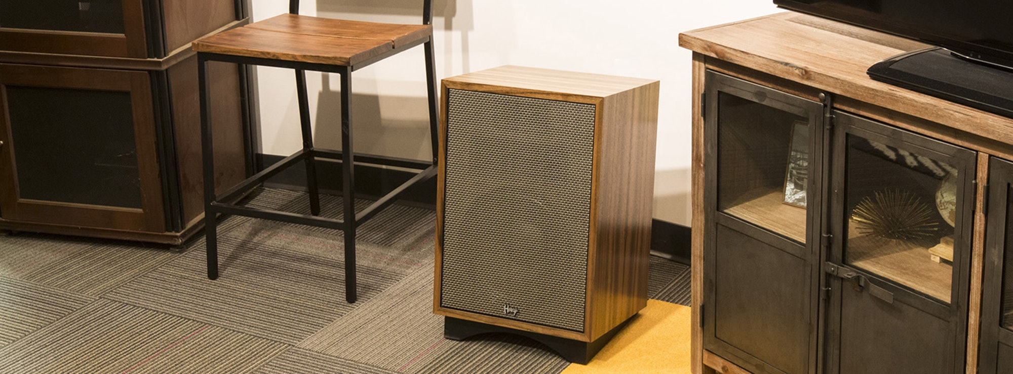 Klipsch Heresy next to a chair and cabinet