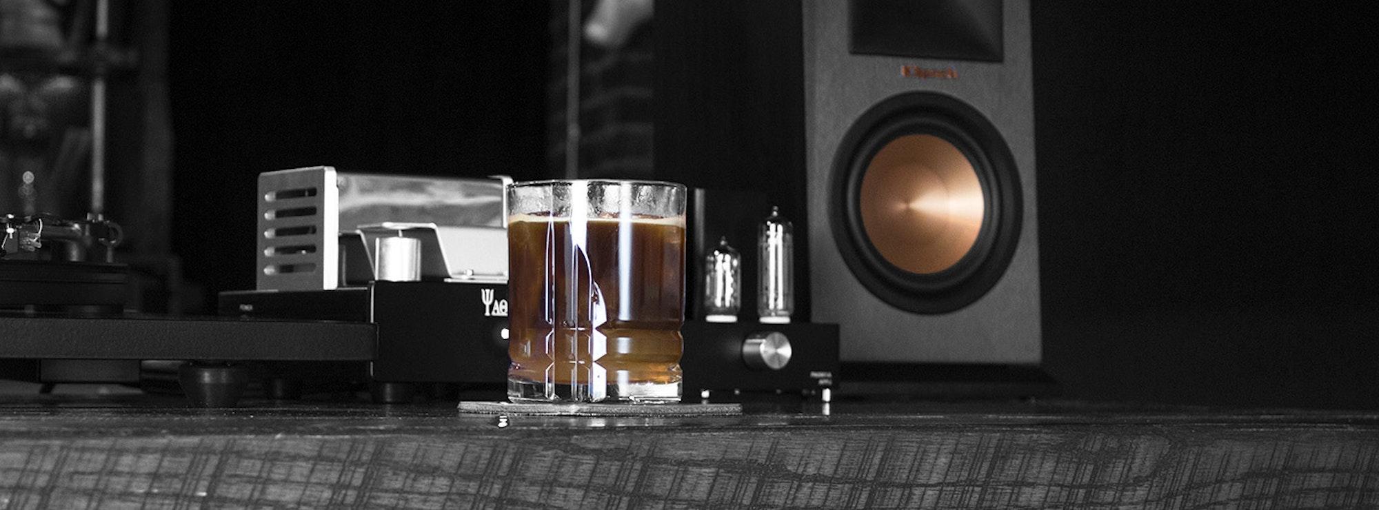 Klipsch bookshelf speaker and U-Turn turntable near a bar