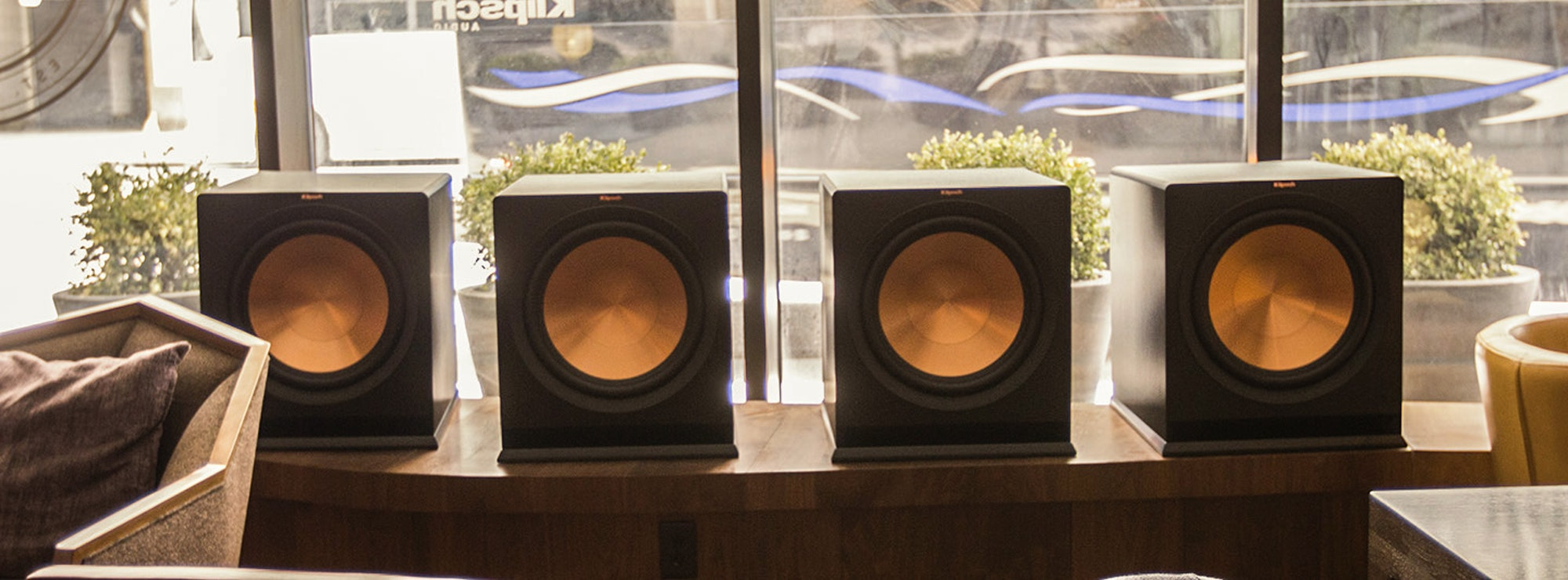 Four subwoofers on a shelf in front of a window