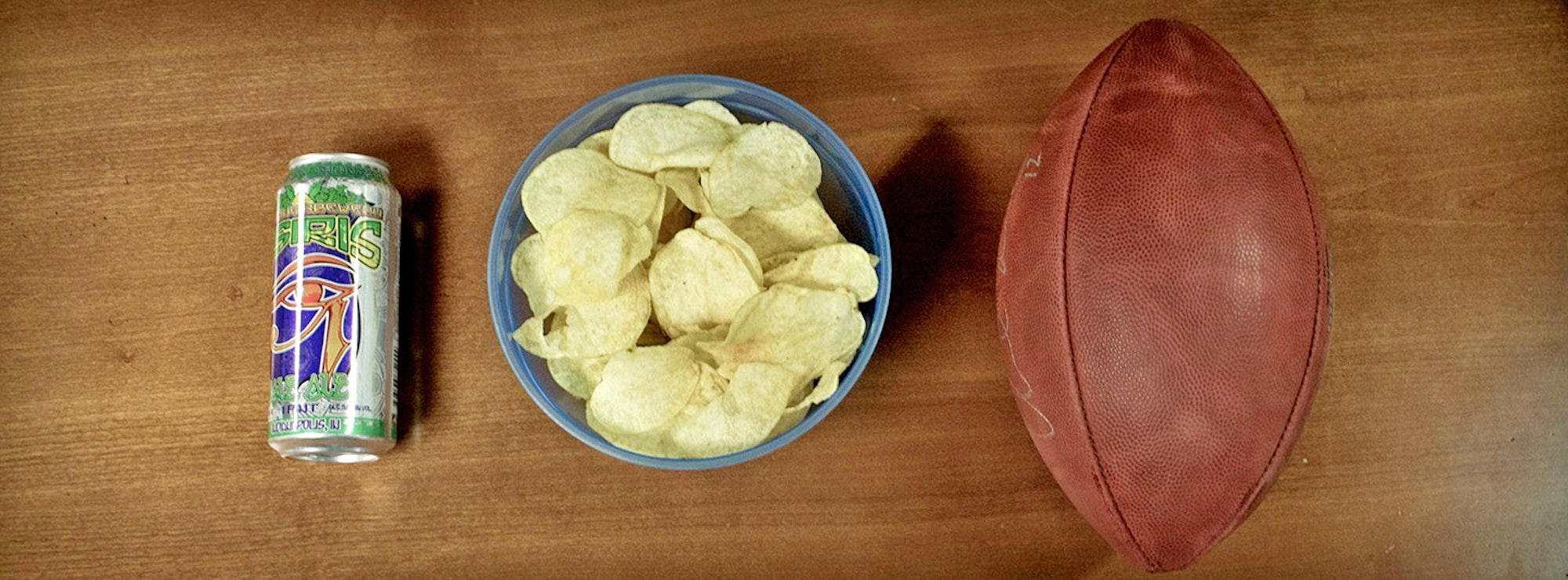Beer, bowl of chips, and a football on a table