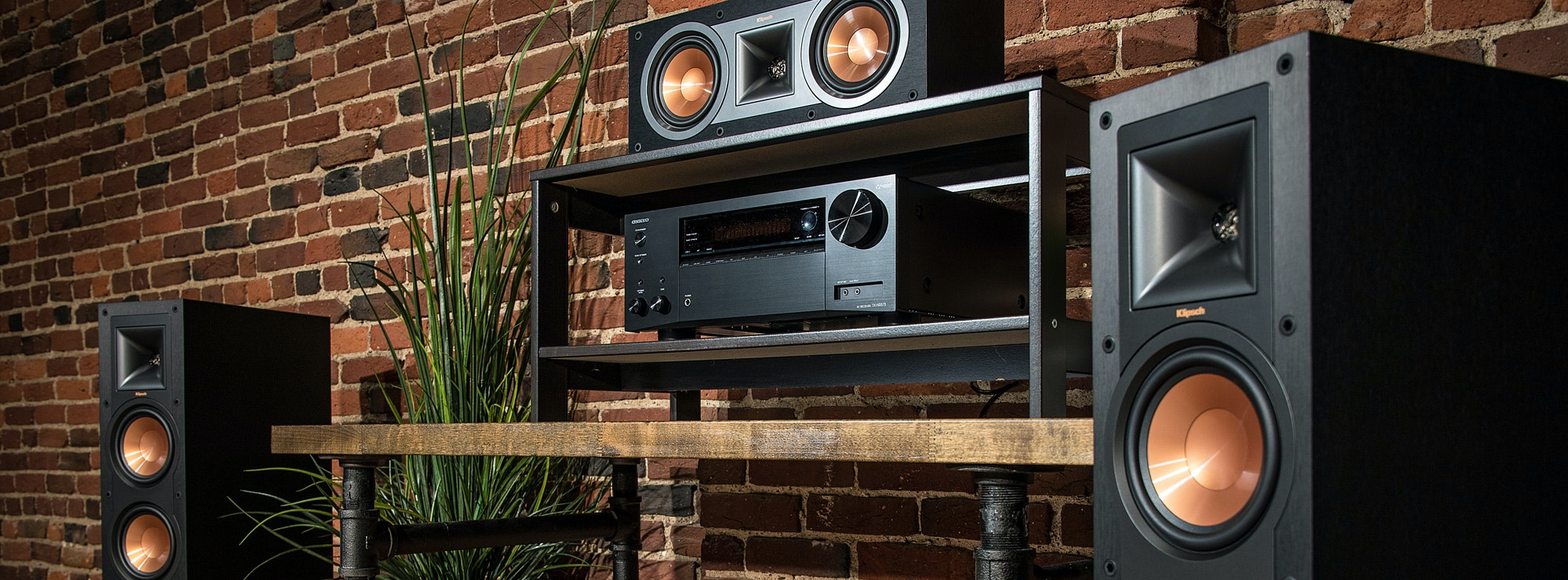 Klipsch speakers next to a wood shelf and a plant