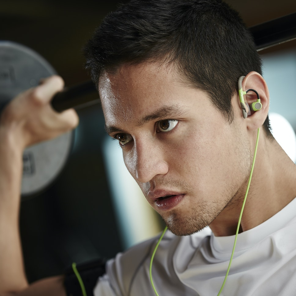 Man lifting weights listening to A5i Sport in-ear headphones