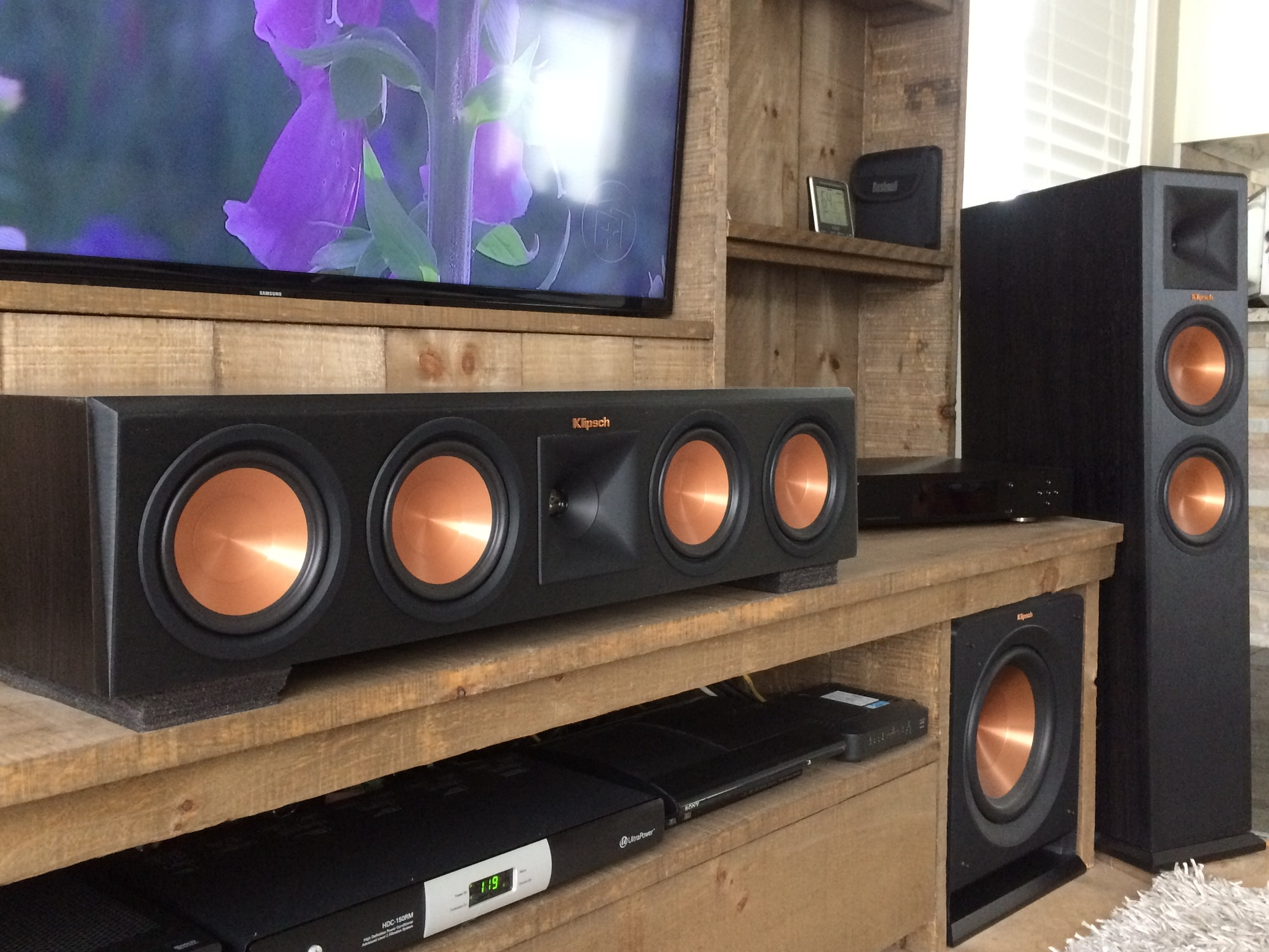 Reference Premiere subwoofer, floorstanding speaker, and center channel speaker as part of a home theater room
