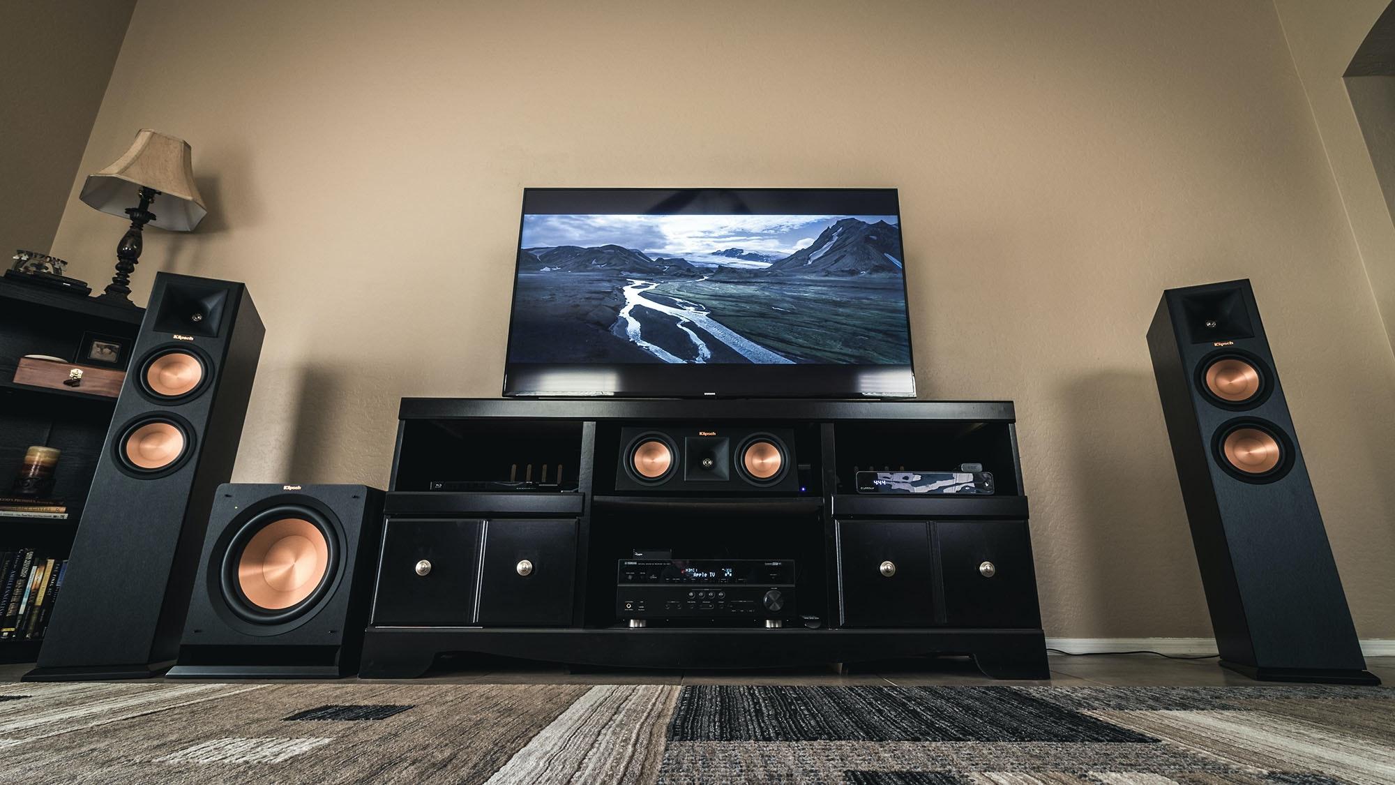 Klipsch surround sound speakers and sub around a tv entertainment center